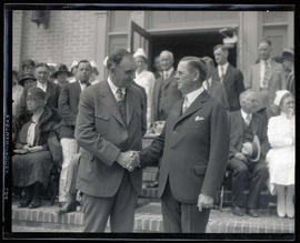 George L. Baker shaking hands with unidentified man at event