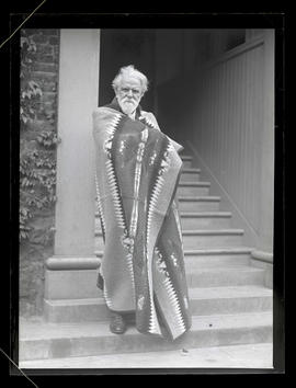 Unidentified man wrapped in blanket, standing in entryway
