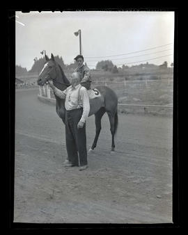 Man, horse, and jockey on racetrack