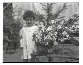Unidentified girl with flowering plant in pot