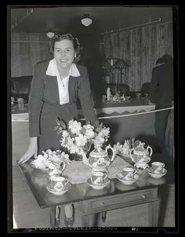 Woman posing with camellias and tea set