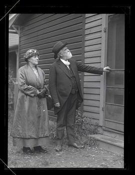 Unidentified woman and man outside house