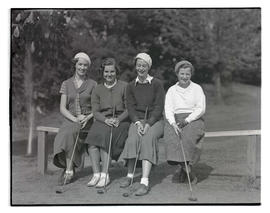 Four unidentified golfers sitting on bench or railing
