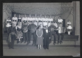 Troupe of performers, some holding instruments