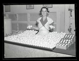 Employee with display of eggs at Ideal Dairy store, Portland