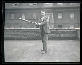 Man in suit, holding baseball bat