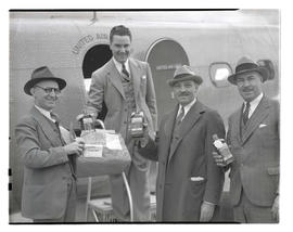 Four unidentified men holding bottles of Seagram's liquor