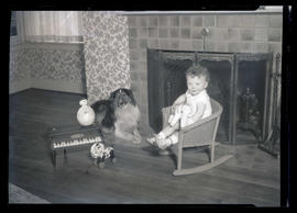 Child from Walker family? and dog in front of fireplace