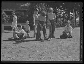 Children at city park playing croquet