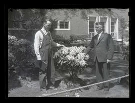 Two unidentified men with rhododendron bush in South Park Blocks, Portland