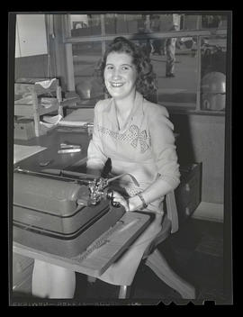 Employee at typewriter during swing shift, Albina Engine & Machine Works, Portland