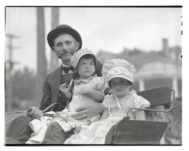 Man and two children in pioneer-themed costumes at parade
