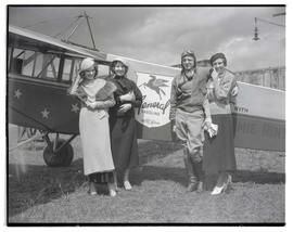 Man and three women with General Gasoline airplane