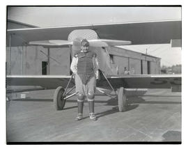 Man in catcher's gear standing in front of airplane