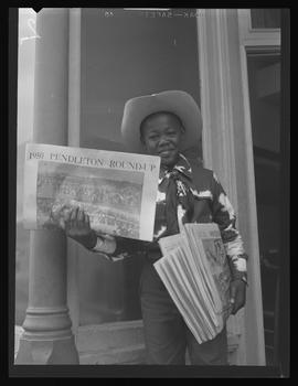 Child with Pendleton Round-Up newspaper