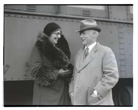 Woman and man next to train car, possibly at livestock show