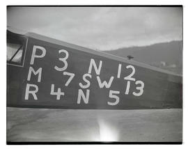 Letters and numbers painted on side of airplane