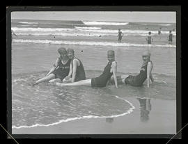 Four women sitting in the surf at Seaside, Oregon