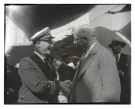 U. S. Navy officer shaking hands with unidentified man