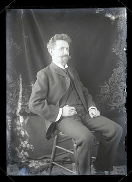 Unidentified man sitting in chair, three-quarters portrait