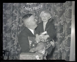 Portland Mayor Joseph K. Carson holding child at Portland Breakfast Club Christmas party for orphans