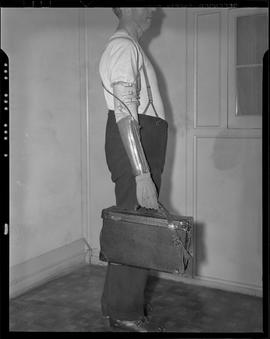 Man with artificial arm holding a bag