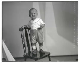Unidentified toddler standing on chair, full-length portrait