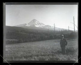 Unidentified man in field with view of Mount Hood