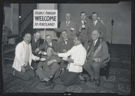 Comedians Olsen & Johnson posing with group of unidentified men