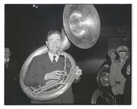 Man carrying sousaphone and holding cigarette