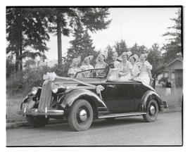 Festival queen and court? sitting in open-topped car