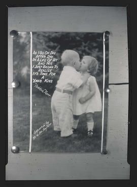 Christmas card from Mr. and Mrs. Roy Norr, showing young children kissing