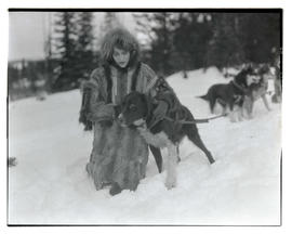 Unidentified woman in fur coat, kneeling in snow next to dog