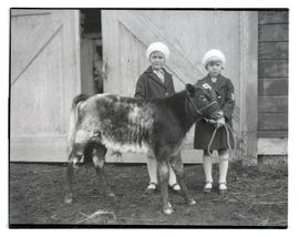 Two girls with calf