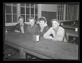Four workers seated at table during swing shift, Albina Engine & Machine Works, Portland