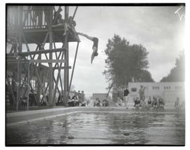 Diver in midair above pool