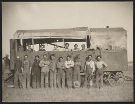 Group posing by wagon in field