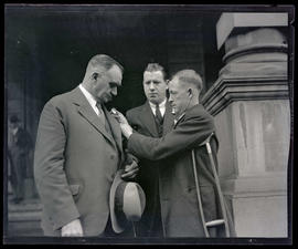 George L. Baker receiving flower pin from unidentified man at Portland City Hall