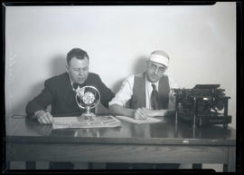 Crookham and Kirkhan at table with microphone and typewriter