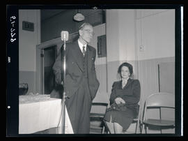 Man standing next to microphone with seated woman