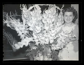 Young woman posing with flower arrangement