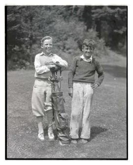 Two boys posing with golf clubs