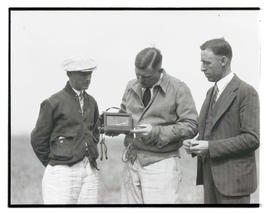 L. B. Hickam and two unidentified men examining barograph for Rankin endurance flight?