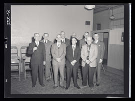 Group of men standing in room with chairs