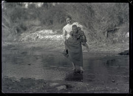 Irene Finley carrying William Jr. across a creek