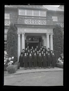 Graduates in caps and gowns, standing outside Marylhurst College administration building