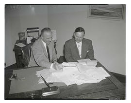 Portland Gas & Coke Co. vice president R. G. Barnett and Sandburg looking at pile of documents
