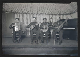 Four musicians seated on stage, holding instruments