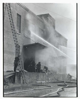 Firefighters outside unidentified burning building