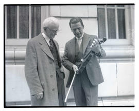 Albert Spalding showing violin to unidentified man